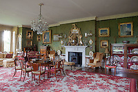 A grand drawing room hung with patterned green flock wallpaper. A glass fronted cabinet displays a collection of fans on the right