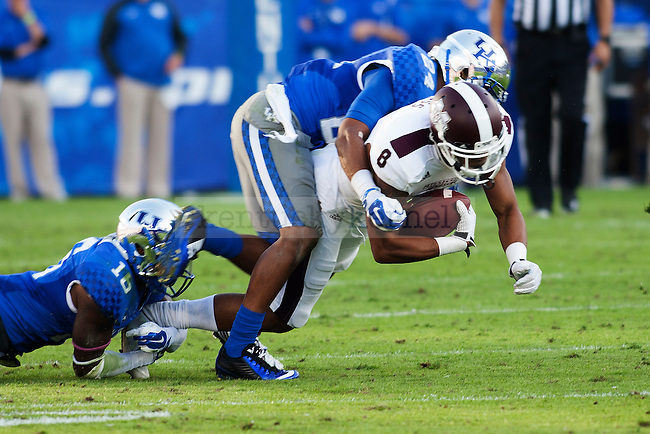 Cornerback Cody Quinn (16) and cornerback Blake McClain (24) of the Kentucky Wildcats tackle a wide receiver during the second half of the game against the Mississippi State Bulldogs at Commonwealth Stadium on Saturday, October 25, 2014 in Lexington, Ky. Mississippi State defeated Kentucky 45-31.Photo by Michael Reaves | Staff