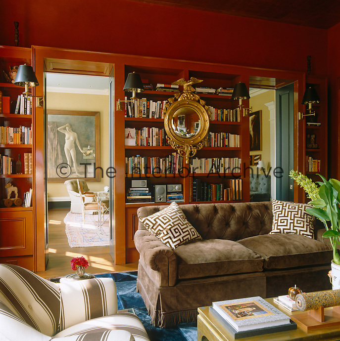 The library is decorated in a burnt orange with a collection of books arranged on open shelves lit by integral shaded lamps