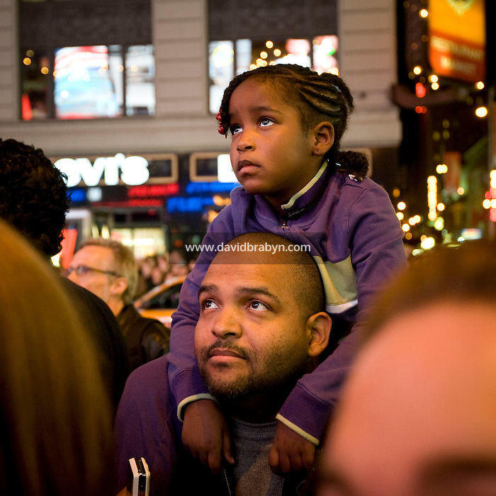 5 year-old Persi Valdivieso sits on her father Rafael's shoulders to watch television coverage of the 2008 US presidential election results on a giant screen on Times Square in New York, NY, United States, 4 November 2008.