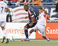 D.C. United midfielder Luis Silva (12) stretches to tackle New England Revolution defender Andrew Farrell (2). In a Major League Soccer (MLS) match, the New England Revolution (blue) defeated D.C. United (white), 2-1, at Gillette Stadium on September 21, 2013.