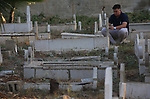 Palestinians visit the grave of their relative at a cemetery on the first day of Eid al-Fitr in the West Bank city of Nablus on June 15, 2018. Eid al-Fitr marks the end of Muslim's holy fasting month of Ramadan when faithfuls abstain from eating, drinking, smoking and sexual activities from dawn to dusk. Photo by Ayman Ameen
