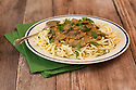 Beef Stroganoff served with noodles in a white dish