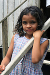 South America, Brazil, Amazon. Young girl in front of her home on the Amazon River.