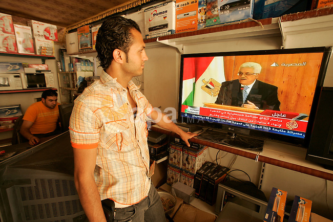Palestinian youths watch on TV the signing of the political reconciliation agreement between Fatah and Hamas at a shop in the southern Gaza Strip town of Rafah on May 04, 201, as Palestinians in the West Bank and Gaza Strip gather to celebrate and welcome the reconciliation deal signed by the bitter rival movements Hamas and Fatah in Cairo. Photo by Abed Rahim Khatib