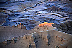 The setting sun illuminates a rock formation in Cainville Badlands, Utah, USA