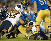 Hardy Nickerson of California loses his helmet while tackling UCLA running back Paul Perkins during the game at Rose Bowl in Pasadena, California on October 12th, 2013.   UCLA defeated California, 37-10.