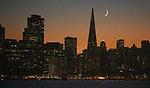 Crescent moon sets behind the San Francisco skyline as seen from Treasure Island, California.