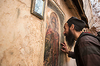 Mount Athos - The Holy Mountain.<br /> A monk stops and prays at the icon of The Virgin Mary in Karoulia. <br /> <br /> Photographer: Rick Findler