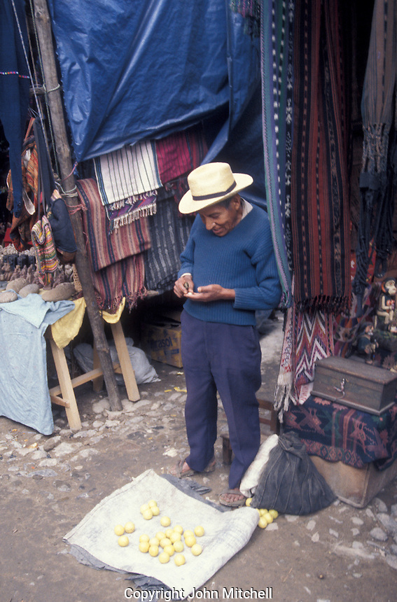 Elderly Maya man counting his earnings at the Sunday market in Chichicastenango, Guatemala