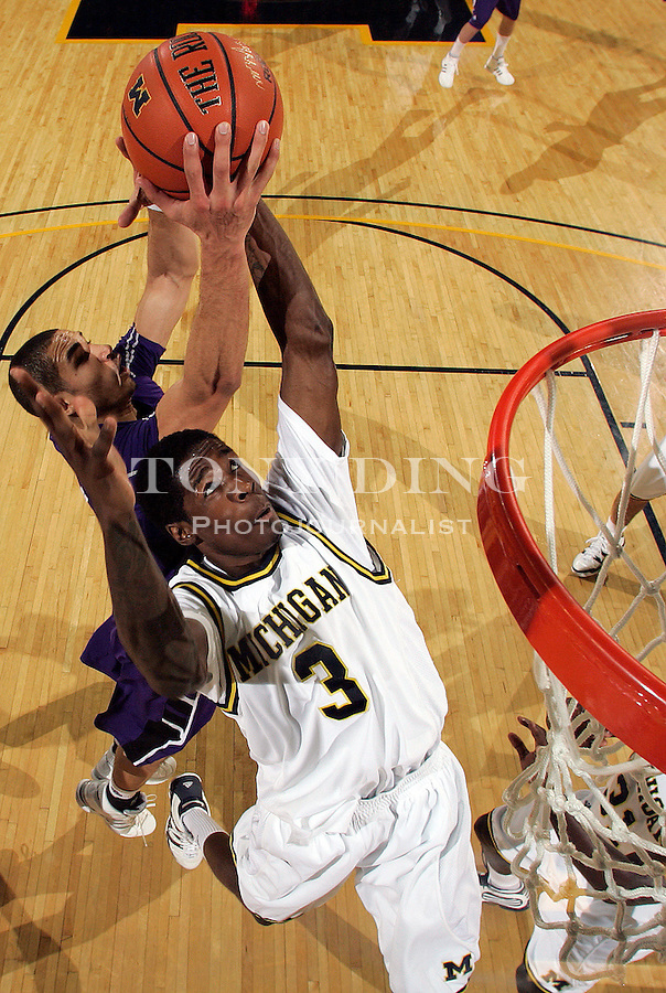 Michigan guard Manny Harris (3) attempts to block a shot from Northwestern guard Drew Crawford, back, in the first half of an NCAA college basketball game, Sunday, Jan. 10, 2010, in Ann Arbor, Mich. (AP Photo/Tony Ding)..***RETRANSMIT TO CORRECT NAME OF NORTHWESTERN PLAYER**