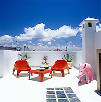 A startling white Moroccan roof terrace with red fibre-glass table and chairs against a bright blue sky