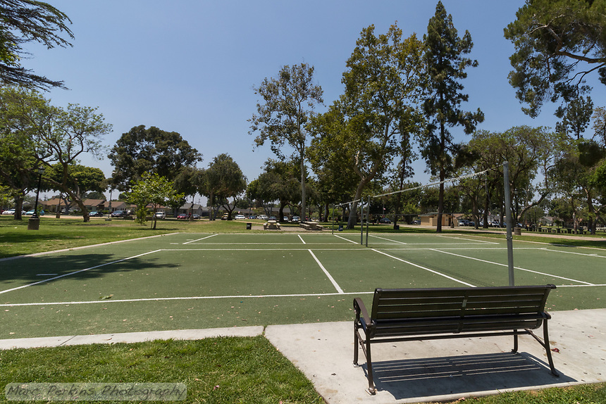 A bench sits alongside the artificial turf volleyball courts at South Gate Park, just calling out for passers by to sit and enjoy a game.