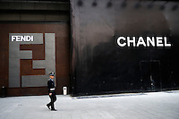 Chinese security guard walks past FENDI and CHANEL stores to be decorated at Sing Kong Place in Beijing CBD. Sing Kong Place is one of the most luxurious shopping centers in Beijing, having successfully attracted 938 international class..