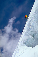 A woman climber on the snow covered face of Gasherbrum II with blue sky and clouds in the background. Gasherbrum II is part of Karakoram in the Himalayan Mountains of Pakistan.
