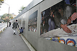 Nov 10, 2009 - Tokyo, Japan - A father and his son walk past large pictures depicting the collapse of the Berlin Wall along the wall of the German Embassy in Tokyo.