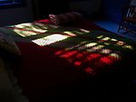 Day 17: self isolation/covid 19/2020. Afternoon sun creates a stained glass effect on my bed quilt. Make the bed every day, keep a schedule, complete tasks, and enjoy the brilliance of beautiful light on an ordinary afternoon during an extraordinary time.