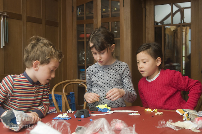 Berkeley CA Siblings, five and seven and girl friend, seven, working cooperatively on clay construction at home MR