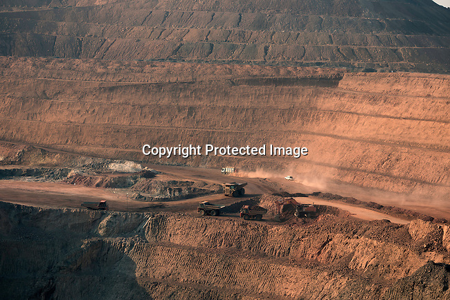 KOLWEZI, DRC- JULY 7: The sun sets on one of the open pit copper mines at Mutanda Mining Sarl on July 6, 2016 in Kolwezi, DRC. The mine is owned (69%) by Glencore, an Anglo-Swiss multinational commodity trading and mining company. The mine is mainly producing copper but also some cobalt. The mine employs about 3,500 people and its located in Luabala Province in Southern DRC. A truck carries a load of ore to the processing plant. (Photo by Per-Anders Pettersson)
