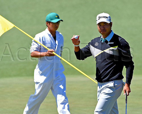 09.04.2016. Augusta, GA, USA.  Hideki Matsuyama, right, acknowledges the applause of the gallery after making a putt on the 2nd green during the third round of the 80th Masters at the Augusta National Golf Club in Augusta, Ga., on Saturday, April 9, 2016. At left, caddie Daisuke Shindo, places the pin