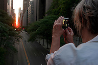 New York, NY -  30 May 2010 Woman taking a snapshot of Manhattanhenge over 42nd Street. ..From Wikipedia: Manhattanhenge (sometimes referred to as the Manhattan Solstice) is a semiannual occurrence in which the setting sun aligns with the east-west streets of the main street grid in the borough of Manhattan in New York City. The term is derived from Stonehenge, at which the sun aligns with the stones on the solstices. It was coined in 2002 by Neil deGrasse Tyson, an astrophysicist at the American Museum of Natural History. It applies to those streets that follow the Commissioners' Plan of 1811, which laid out a grid offset 28.9 degrees from true east-west.