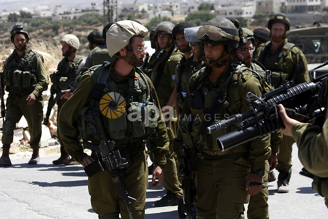 Israeli soldiers stand guards as Palestinian, Israeli activists and International activists protest against Israel's separation barrier in the West Bank village of Maasarah, near the biblical town of Bethlehem, on May 28, 2010. Photo by Mamoun Wazwaz