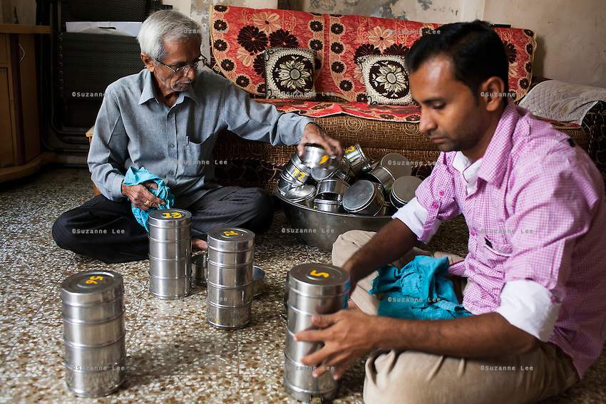 Archana's husband (right) and father-in-law (left) cleans tiffin containers, as she continues to work with Dr. Nayana Patel, catering specially prepared tiffin meals to the surrogates and Akanksha IVF and Surrogacy clinic staff, which she prepares in her house with her family in Anand, Gujarat, India on 11th December 2012. Photo by Suzanne Lee / Marie-Claire France