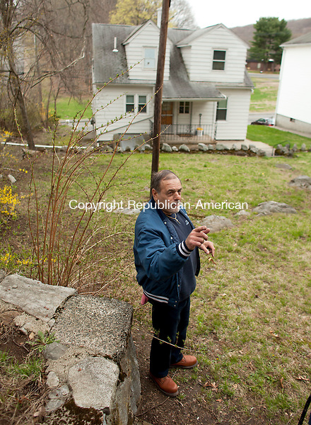 NAUGATUCK, CT-29 April 2014-042914BF03- Vin Cascella describes the water problem on his property on Andrew Avenue in Naugatuck. Cascella lives next door to Maria Novo and her son Americo Novo who claim water has damaged their home and property. The Novo's claim that after construction work on the Garden Homes Management Corporation owned apartment complex last year, water has been a problem on their property and has damaged their home. The water pipes sticking up in the driveway are one of the problems they say are caused by the water.   Bob Falcetti Republican-American