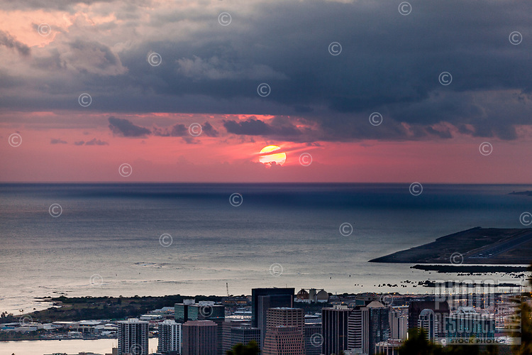 An aerial view of the sun setting in a red sky topped by stormy clouds, with the buildings of downtown Honolulu in the foreground, as seen from Tantalus Lookout, Pu'u 'Ualaka'a State Park near Roundtop Drive, O'ahu.