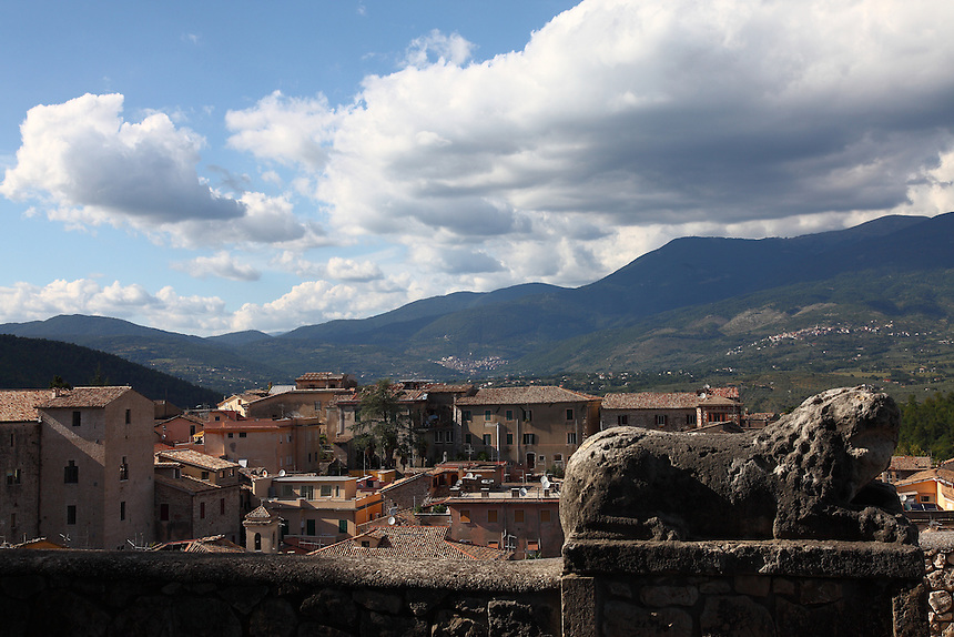 A view of a part of Alatri from the garden at the top of the citadel's hill, with the remains of a sculpted lion in foreground and mountains in the distance, in a sunny day, under a partially clouded sky. Digitally Improved Photo.