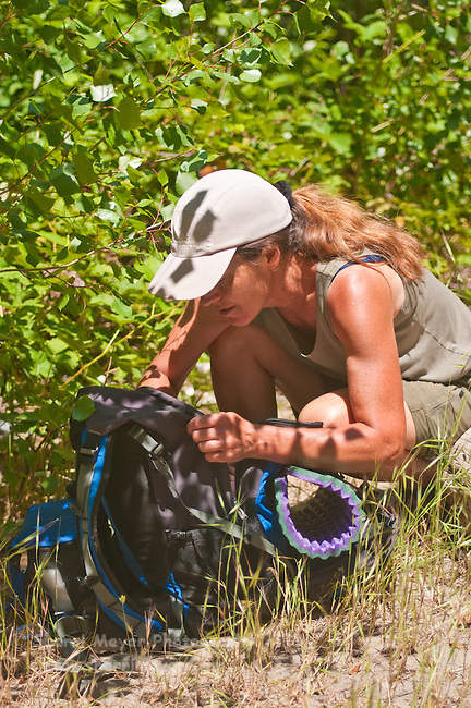 Hiker unpacking her picnic lunch from her daypack, North Fork of the American River, Weimar, California.