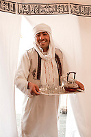 A waiter serves tea in a tented bedroom at the Akakus Magic Lodge