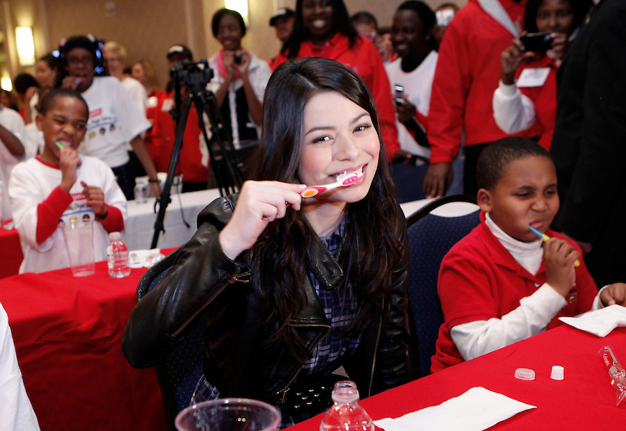 """Actress and musician Miranda Cosgrove participates in a """"brush-a-thon"""" as she attends a Colgate event, """"100 million smiles Celebration"""" in New York October 27, 2009. Natalie Behring / AP for Colgate-Palmolive Company"""