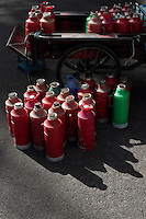 Hot water in kettles are delivered to a local restaurant by a tricycle in Nanjing, Jiangsu province, China, November 2012.