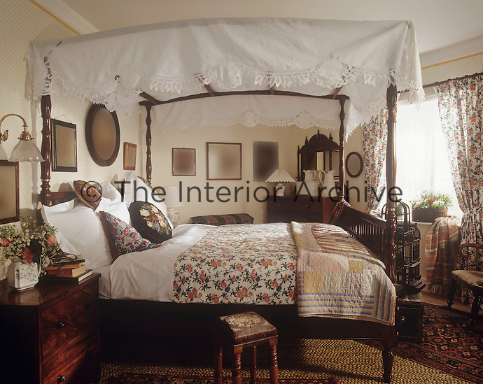 A country bedroom with a wooden four poster bed. A floral bed cover matches the curtains at the window. A chest of drawers stands in one corner of the room.
