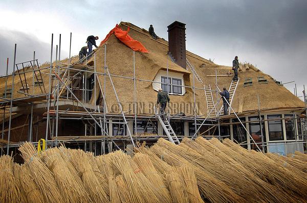 """ALMERE - In het zuiden van Almere werken Hongaarse medewerkers van rietdekkersbedrijf Wincoop aan een door Guma Bouw gebouwd woonhuis. Het door A. Th. Maas ontwerpen gebouw is één van de vele onder architectuur gebouwde woningen die verrijzen op het prestigieuse woningbouwproject Overgooi. Naast het Waterlandse Bos heeft de gemeente Almere een terrein voor woningbouw aangewezen, dat """"niet voor iedereen weggelegd."""" Het project heeft """"een hoog ambitieniveau, biedt kwaliteitsarchitectuur"""" en levert daarom """"geen doorsneewoningen"""" op, maar """"droomvilllas zoals notariswoningen en landhuizen met rieten kap."""" Voor de liefhebbers heeft de gemeente nog enkele tientallen kavels in de verkoop. COPYRIGHT TON BORSBOOM"""