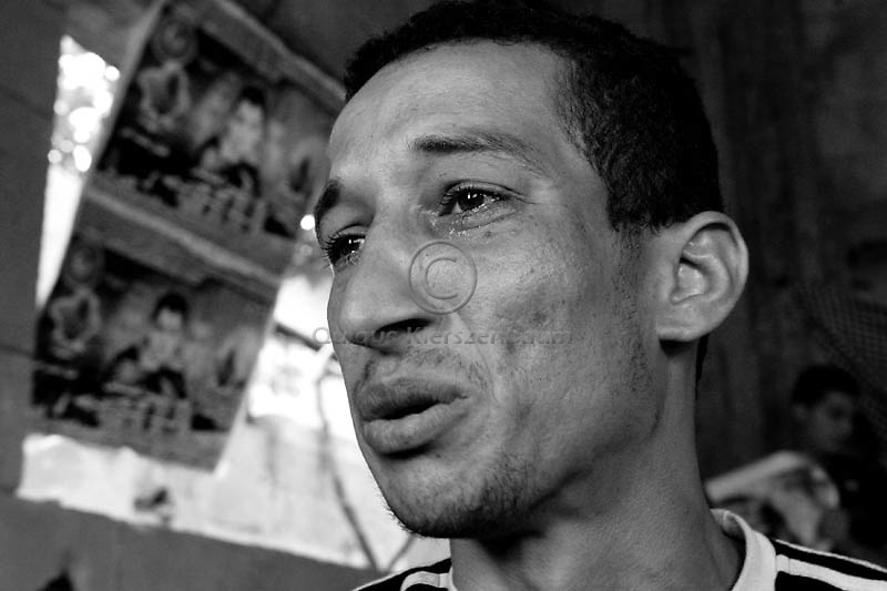 Hamdi Aman, 28 cries as he mourns the death of  his wife, his mother and one of his sons, in the family home in Gaza City, May 28, 2006. Hamdi and his son Mumin survived an Israeli air strike as Israel Air Force targeted the Islamic Hamas leader Mohammed Dadouh, when the family was in a car next to the jeep of the Islamic Jiahad leader Saturday, May 20, 2006. As a result of the strike Hamdi's wife, Naima, his mother Hanan and his son Muhaned were killed. A seven-year-old daughter Mariya was seriously injured in the attack also. Photo by Quique Kierszenbaum