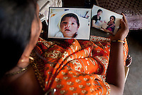 """Shardaben holds photographs of her surrogacy jobs...Shardaben Kantiben, 31; Husband is Kantibhai Motibhai (37).3 children --- 2 girls -  Usha(15) and Lakshmi (18, in pink); 1 boy, Chintan (17).- Education costs for all three come to Rs. 15,000 per year.- Shardaben was a two-time surrogate. First time she gave birth to twin girls for a Taiwanese couple and the second time a boy for an Indian couple from America (photo on TV set because she's proud that it was a boy).- The second time she became emotional and they got a gold ring of Rs. 1,500 made for the boy, which they presented to the biological parents. They are not in touch with either couple..- From the two surrogacies, they earned a little over 700,000rupees..-200,000rupees will be given as dowry for Lakshmi's wedding..- They leased agricultural land (Rs. 2 lakhs for five years) which earns them Rs. 60,000-70,000 a year; they bought two buffaloes worth Rs. 60,000 and make almost 6000-7000 per month selling milk; they bought a motorbike for Rs. 25,000; they put some money into house repairs and the construction of toilets, and opened a fixed deposit in Shardaben's name for Rs. 1.5 lakh and one in the name of their son, Chintan, for Rs. 25,000..Quotes..""""Everyone says they'll keep in touch and take down addresses and phone numbers but nobody looks back. And I guess it works well. Our main interest was in the money. Their main interest is in the baby."""" - KantiBhai.""""Their rules apply at the surrogate house. It does curtail the freedom. When I used to go, everybody would just be lying. They count the days when they can go back."""" - Kantibhai.""""Ours is natural birth but surrogacy is a man-made pregnancy. There's a lot of risk. She must have taken at least 300 injections."""" - Kantibhai of his wife...The Akanksha Infertility Clinic is known internationally for its surrogacy program and currently has over a hundred surrogate mothers pregnant in their environmentally controlled surrogate houses. .Photo by Suzanne Lee"""