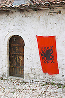 The Albanian flag, red with black double headed eagle, against a white washed stone wall. Old wooden door. Berat upper citadel old walled city. Albania, Balkan, Europe.