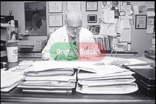 doctor at desk with paperwork