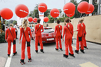 Switzerland. Canton of Neuchâtel. Neuchâtel. Grape Harvest Festival. A group of young women, dressed in red, holding red balloons, skate on the concrete road. They are making the promotion for a garage selling Alfa Romeo cars.  © 2006 Didier Ruef