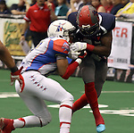 SIOUX FALLS, SD - JUNE 7 Troy Harrison #22 from the Sioux Falls Storm has the ball stripped, then returned for a touchdown by Frankie Solomon, Jr #15 from the Texas Revolution in the second quarter of their game Saturday night at the Sioux Falls Arena. (Photo by Dave Eggen/Inertia)