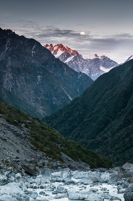 Full moon with sunrise on Southern Alps and rocky Butler River near Ice Lake, Westland National Park, West Coast, New Zealand
