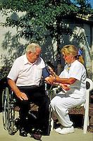 Nurse takes blood pressure of elderly man in wheelchair.
