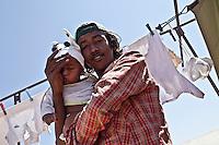 Tunisie RasDjir Camp UNHCR de refugies libyens a la frontiere entre Tunisie et Libye refugees camp  Tunisian and Libyan border  Tunisia campo profughi di RasDjir al confine tra tunisia e Libia  Jeune avec son fils Giovane rifugiato tiene un bambino in braccio