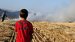 An Israeli boy is seen looking at a firefighter putting out a wild fire in the fields on the outskirts of the town of Afula, April 25th, 2009. Photo by : Michael Salman / JINI..