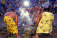 "Four Hawaiian men dressed in lavalavas ( traditional  garments) pull a roasted pig out of the """"imu"""" or earth oven at the Kona Village Resort. Seated tourists watch the ceremony."