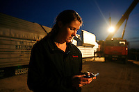 Project leader Kelly Cummins sends a phone message while monitoring the loading of casks containing highly enriched uranium (HEU) from trucks onto an armoured train in Almaty. The removal of Kazakhstan's HEU is part of the U.S. Global Threat Reduction Initiative (GTRI), where Kelly Cummins works, which tries to secure nuclear material around the world to prevent their misuse.