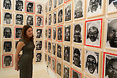 27 February 2014, London, United Kingdom. Pictured: A Gallerist stands in front of a series of 85 photos entitled: 28 MM - Women are Heroes, Action in Kibera Slum by artist JR. The Art14 Art Fair at Olympia Grand Hall, London, opens its doors to the public from 28 February to 2 March 2014. Art14 London features 180 galleries from 40 countries with works from emerging talents to modern masters.