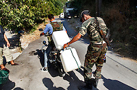 Free Syria Army soldiers unload two plastic tanks used to carry petrol to supply the villagers around the Al Kassab region of northwestern Syria...The Al Kassab region of northwestern Syria is considered the front line in the war against the Assad regime in this region of the country. This is the home to many sunni Muslims that are suffering the brunt of the shelling by the Assad army and air force - electricity was cut off months ago and basic food items along with petrol and potable water are increasingly in short supply. ..Still, the many groups that compose the Free Syria Army (FSA) in this region press on as the winter months approach. Most of the members of the FSA in this area are farmers, cell phone salesmen, clerks, carpenters, school teachers - most of them had little or no combat experience prior to joining the opposition army. Weapons and ammunition are also increasingly hard to come by as the price for bullets has skyrocketed since the conflict began 18 months ago. Rumors of an assault on this region by the Assad regime are part of everyday conversation in the villages that for the past few weeks have managed to keep the regime's army tanks and infantry out of their homes. ..© Javier Manzano